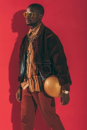 Photo for Stylish african american man in sunglasses holding golden basketball ball and looking away - Royalty Free Image