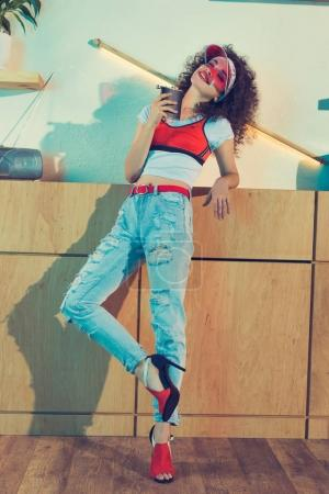 Photo for Smiling fashionable woman with hip flask in hand and eyes closed - Royalty Free Image