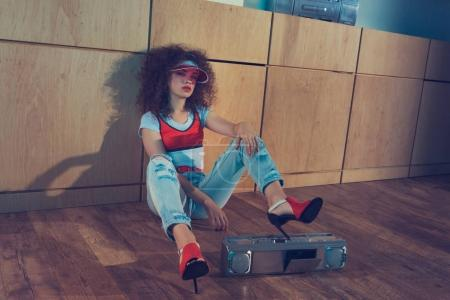 Fashionable woman with boombox sitting on floor