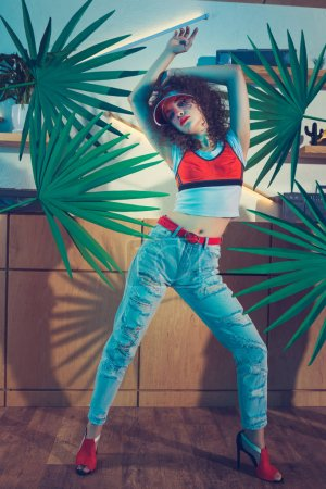 Photo for Fashionable young woman in red cap and stylish clothing - Royalty Free Image