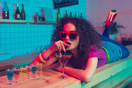 woman in sunglasses drinking cocktail