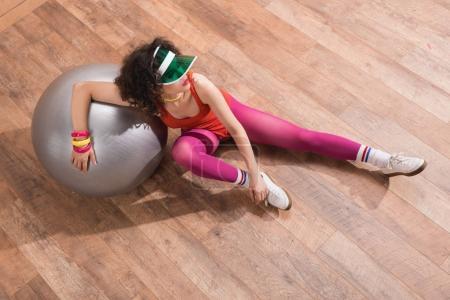 Photo pour Vue grand angle de la femme à la mode en costume de corps lumineux reposant sur la balle de fitness - image libre de droit