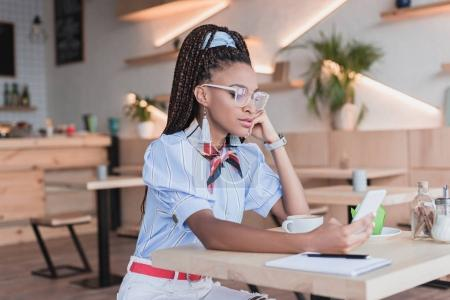 African american woman using smartphone in cafe