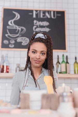 Photo pour Jeune barista afro-américaine debout derrière le comptoir au café - image libre de droit