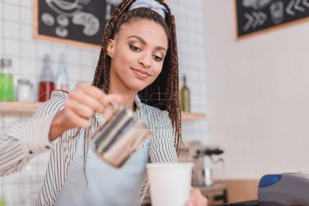 barista pouring milk into coffee