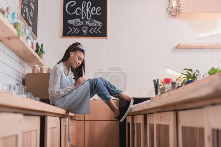 barista sitting on counter with notebook