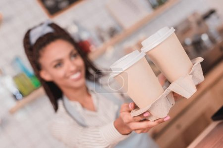 barista handing out holder with cups
