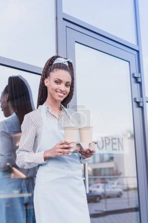 barista holding two paper cups