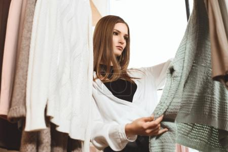attractive girl choosing clothes