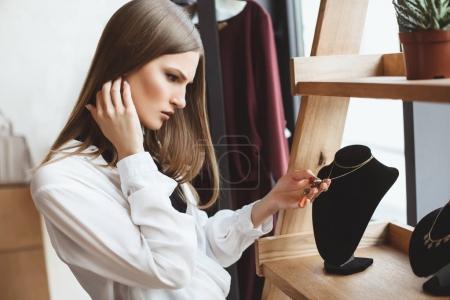 woman choosing necklace