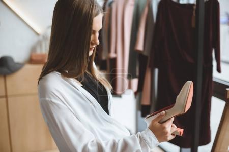 Photo pour Séduisante femme tendance choisissant des talons élégants en boutique - image libre de droit