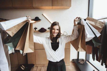 Photo pour Femme élégante souriante tenant des sacs à provisions dans la boutique - image libre de droit