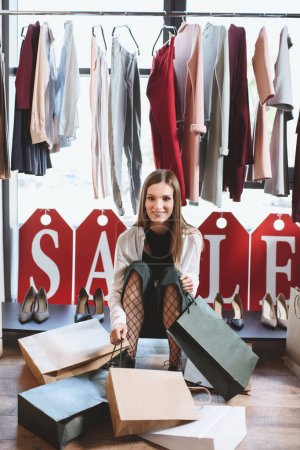 Photo pour Femme shopaholic avec des sacs à provisions en boutique avec des étiquettes de vente - image libre de droit
