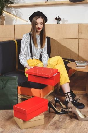 Photo for Attractive fashionable girl choosing footwear in boutique - Royalty Free Image