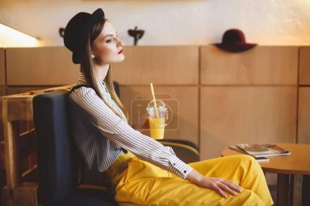 Photo for Beautiful stylish pensive girl in hat with orange juice sitting in cafe - Royalty Free Image