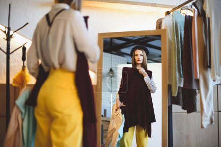 girl in hat choosing clothes