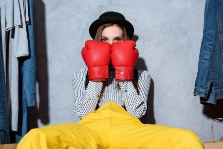 girl in boxing gloves sitting in boutique