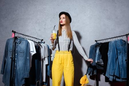 girl in boutique with clothes around