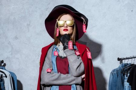 fashionable woman in clothes with sale tags