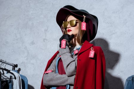 Photo for Woman in sunglasses, hat and different clothes with sale tags - Royalty Free Image
