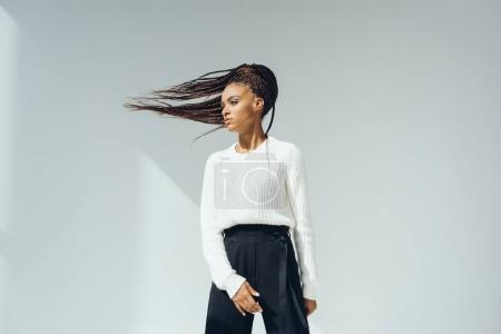 Photo for Beautiful african american woman in white stylish knitted sweater looking away on grey - Royalty Free Image