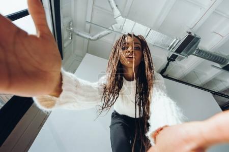 Photo pour Vue à faible angle de belle fille afro-américaine prenant selfie - image libre de droit