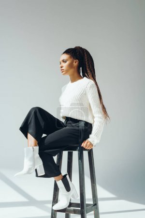 Photo for Attractive african american girl in stylish knitted sweater sitting on stool and looking away - Royalty Free Image