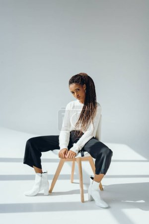 Photo for Beautiful stylish african american woman in fashionable outfit sitting on chair and looking at camera - Royalty Free Image