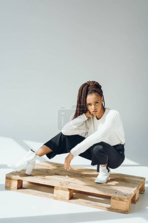 Photo for Young fashionable african american woman posing on wooden pallet in studio - Royalty Free Image