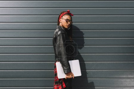 Photo for Fashionable young african american woman in leather jacket holding laptop - Royalty Free Image