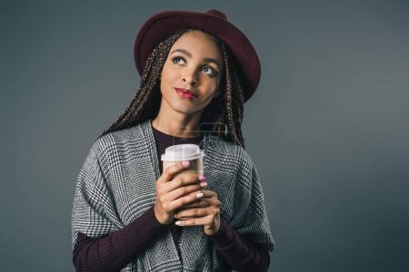 Photo for Pensive african american girl in hat holding coffee to go and looking away isolated on grey - Royalty Free Image