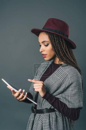 Photo pour Belle fille afro-américaine élégante à l'aide de tablette numérique isolé sur fond gris - image libre de droit