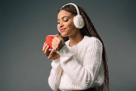 Photo pour Belle fille afro-américaine souriante dans le cache-oreilles fourrure coupe en tenant avec boisson chaude isolée sur fond gris - image libre de droit
