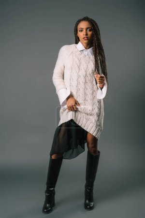 Photo for Stylish african american girl in knitwear looking at camera isolated on grey - Royalty Free Image