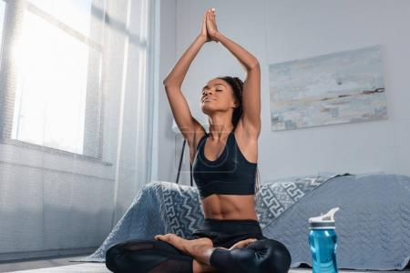 Photo for Attractive african american woman practicing yoga in padmasana pose - Royalty Free Image