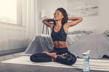 Photo for Woman practicing yoga and relaxing in lotus pose - Royalty Free Image