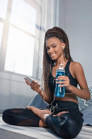 Photo for Young beautiful african american woman with smartphone and water bottle sitting on yoga mat - Royalty Free Image