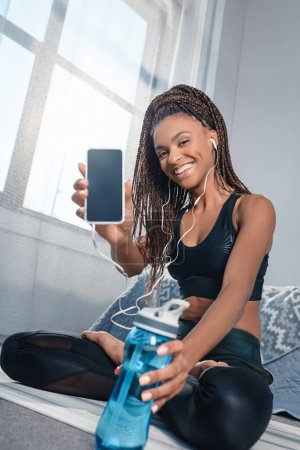 athletic woman showing smartphone