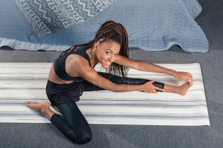 woman stretching leg on yoga mat