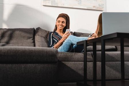 Photo pour Belle femme afro-américaine utilisant un smartphone sur le canapé à la maison - image libre de droit