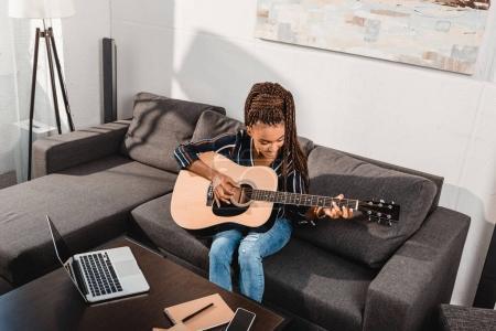 Photo pour Afro-américaine jouer de la guitare tout en étant assis sur le canapé - image libre de droit