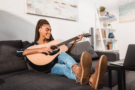 Photo pour Femme afro-américaine jouant de la guitare en position assise sur le canapé - image libre de droit