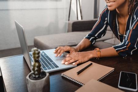 Photo pour Plan recadré de femme afro-américaine en utilisant un ordinateur portable tout en étant assis sur le canapé à la maison - image libre de droit