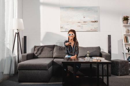 Photo for Happy african american woman watching tv in 3d goggles pointing at camera with remote control - Royalty Free Image