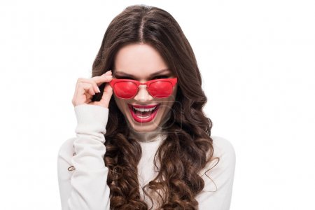 Photo for Young laughing woman with bright makeup looking over her red sunglasses, isolated on white - Royalty Free Image