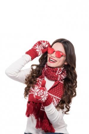 Foto de Joven sonriente en la bufanda y mitones usar gafas de sol opacos rojo y mostrando pulgar arriba, aislado sobre blanco - Imagen libre de derechos