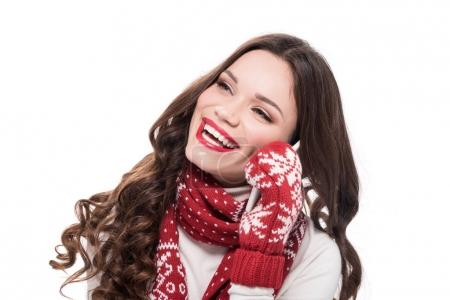 Photo for Young happy woman in scarf and mittens talking on smartphone, isolated on white - Royalty Free Image
