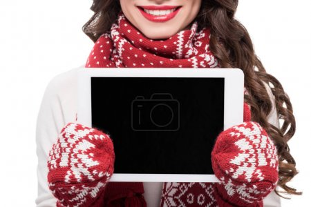 Photo for Cropped shot of young smiling woman in scarf and mittens showing digital tablet screen, isolated on white - Royalty Free Image
