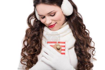 Photo pour Jeune femme souriante en écharpe, gants et cache-oreilles tenant un cadeau, isolé sur blanc - image libre de droit