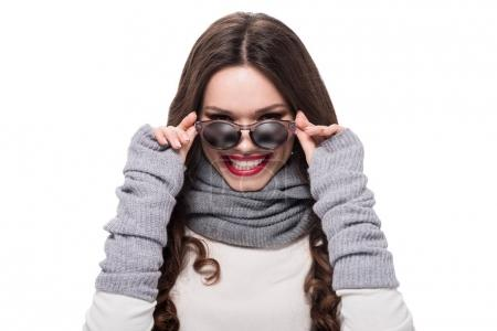 Photo for Young smiling woman in winter attire looking over sunglasses, isolated on white - Royalty Free Image